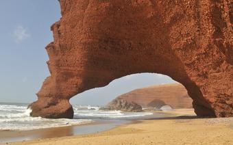 """Plaża wmiejscowości Legzira. Silne fale Oceanu Atlantyckiego wyżłobiły wskałach efektowne """"bramy"""""""